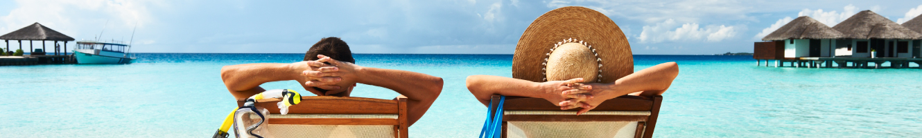 Two people relax in their loungers as they sit on edge of the water of a crystal blue ocean.