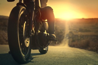 A man sits on a motorcycle on a road during sunset.