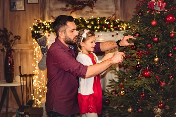 Father and daughter place an ornament on the Christmas tree